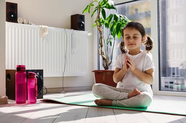 Linda garotinha sentada em uma esteira de ginástica e praticando ioga em posição de lótus contra o fundo