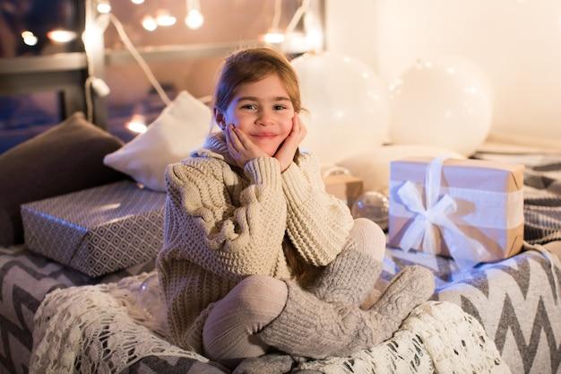 Linda garotinha sentada na cama com um presente nas mãos. instale a caixa de presente de natal no feriado à noite na bela sala interior. ano novo.