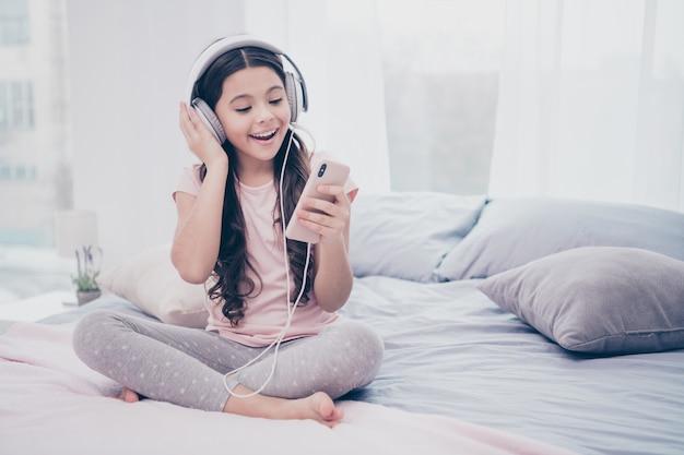 Linda garotinha sentada na cama com um smartphone e fones de ouvido