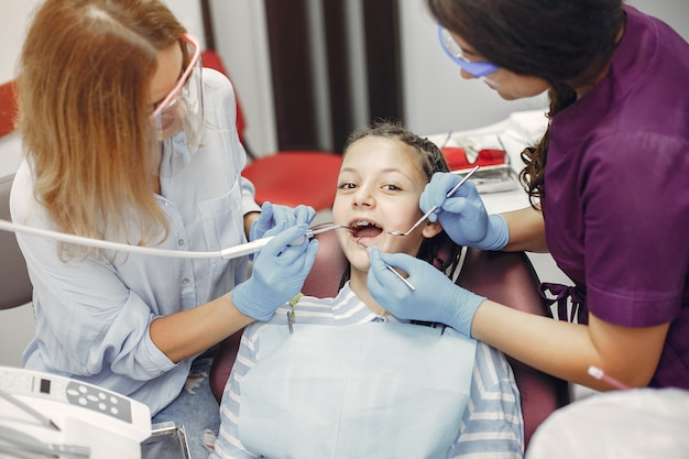 Linda garotinha sentada no consultório do dentista