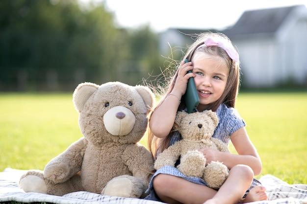Linda garotinha sentada no parque de verão com seu ursinho de pelúcia falando no celular, sorrindo alegremente ao ar livre no verão.