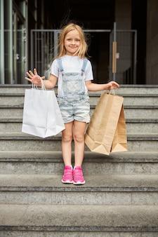 Linda garotinha sorridente segurando sacolas de papel enquanto fica de pé nas escadas ao ar livre