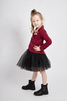 Linda garotinha sorrindo, criança com roupas de outono posa em um fundo branco