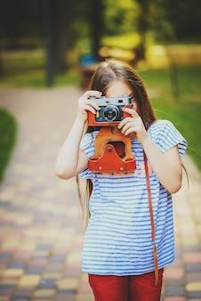 Linda garotinha tira uma foto com uma câmera vintage em uma floresta verde e ensolarada
