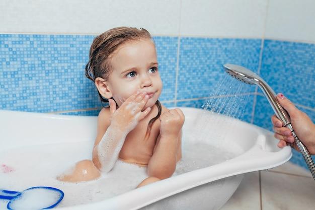 Linda garotinha tomando banho em casa.