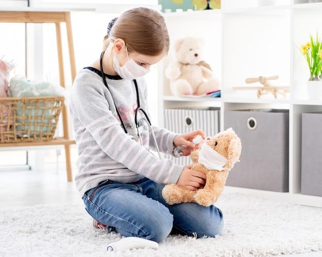 Linda garotinha usando desinfetante no ursinho de pelúcia