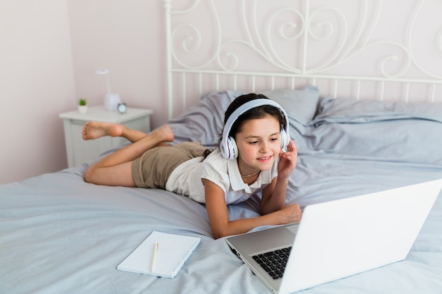 Linda garotinha usando seu laptop