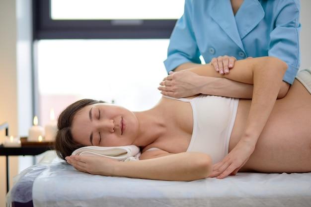 Linda grávida grávida morena desfrutando de massagem nas costas e ombros na sala de esteticista no centro de spa, vista lateral na senhora relaxada deitada na cama com os olhos fechados, descansando