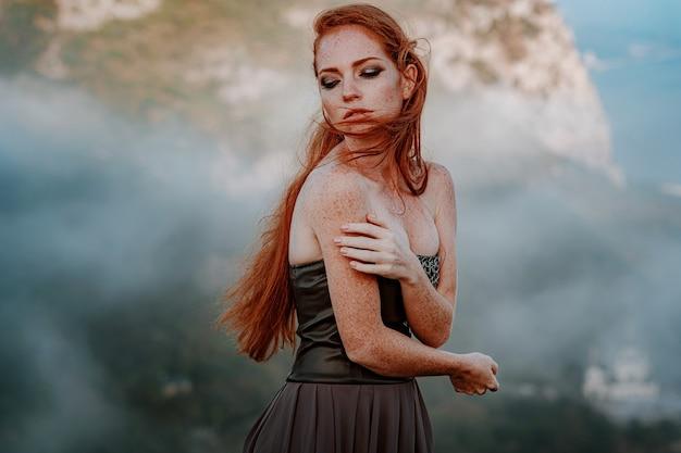 Linda guerreira escandinava mulher ruiva em vestido cinza com corrente de metal Foto Premium