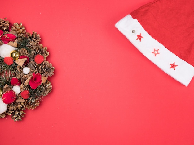 Linda guirlanda de natal com chapéu de papai noel em fundo vermelho. decoração festiva de interiores.