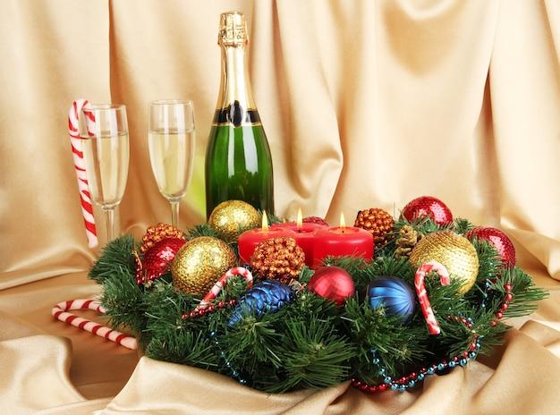 Linda guirlanda de natal em composição com champanhe em fundo de tecido dourado