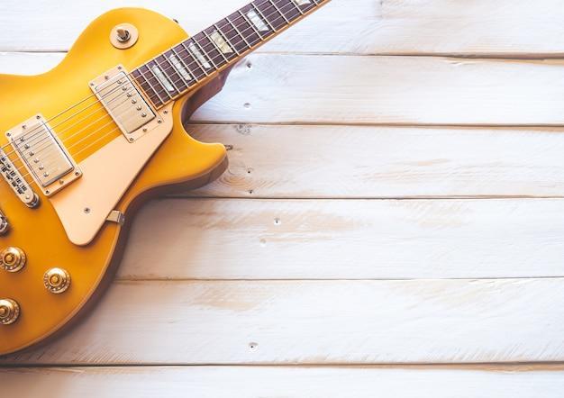 Linda guitarra elétrica dourada clássica em uma mesa de madeira branca.