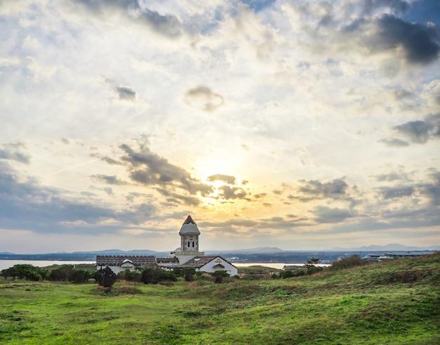 Linda igreja católica na manhã com o nascer do sol e o céu azul em seopjikoji mount jeju island, coréia do sul
