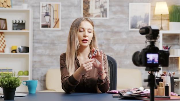 Linda influenciadora de beleza gravando um vlog sobre pincel de maquiagem. maquiador famoso.