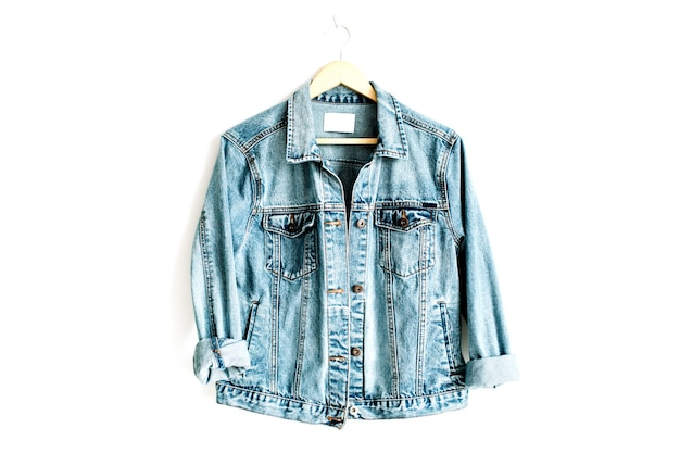 Linda jaqueta jeans azul da moda no cabide perto do branco