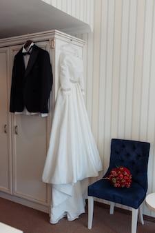 Linda jaqueta preta noivas e noivas vestido pendurado no quarto de hotel