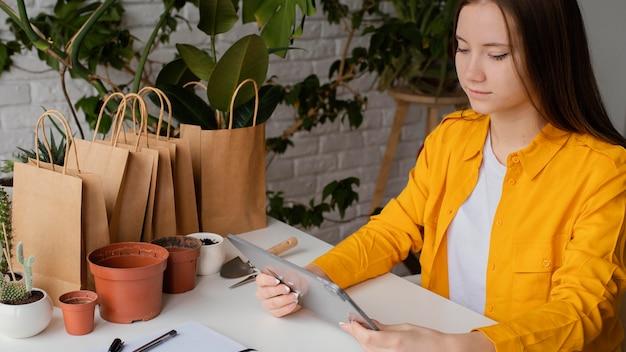 Linda jardineira verificando seu tablet