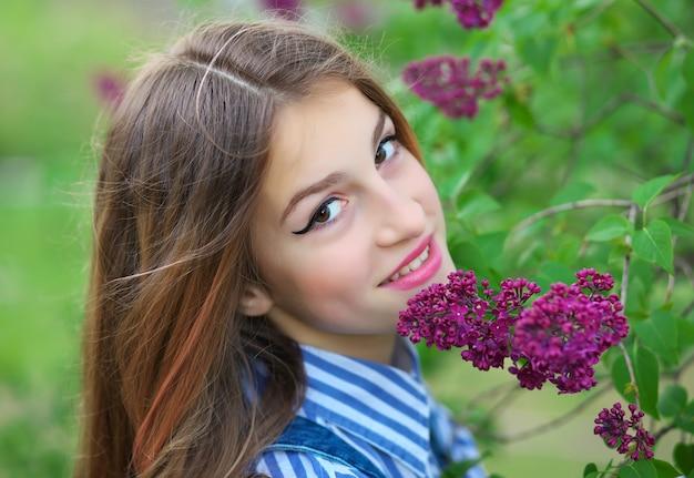 Linda jovem adolescente em pé nas flores lilás.