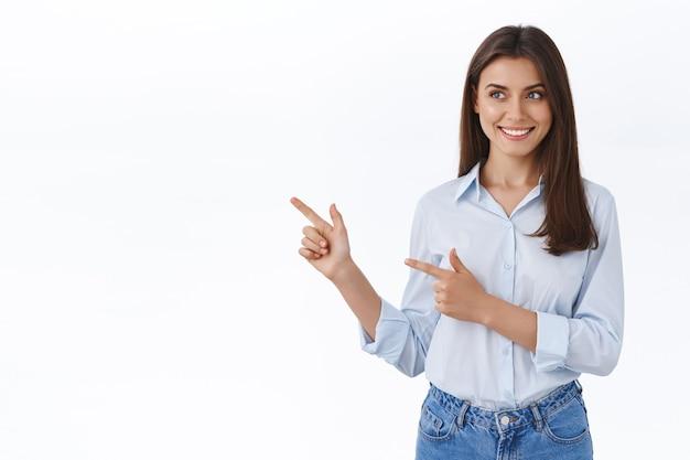Linda jovem adulta com blusa azul apresenta o banner da empresa, amigável e sorridente, apontando olhando para o espaço em branco em branco do seu anúncio, de pé na parede do estúdio