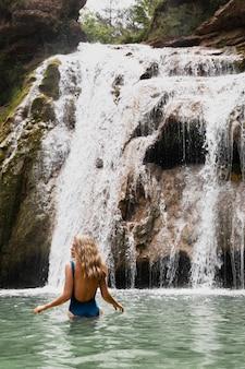 Linda jovem adulta perto da cachoeira