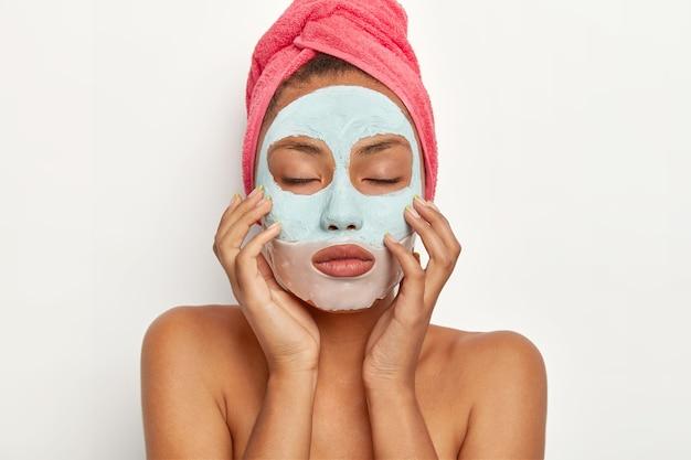 Linda jovem afro-americana aplica máscara facial de argila no rosto, toca a pele suavemente, mantém os olhos fechados, usa toalha enrolada na cabeça, fica de pé com os ombros nus, faz tratamentos de beleza