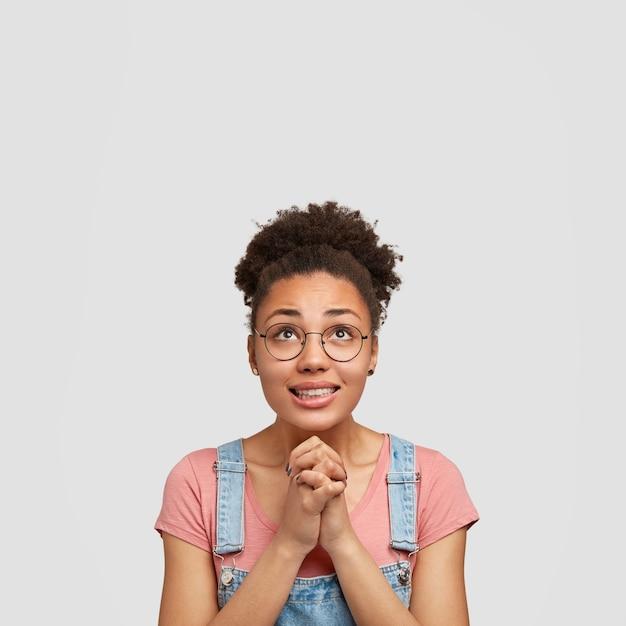 Linda jovem afro-americana com expressão suplicante, olha para cima, tem sorriso gentil, acredita fortemente no bem-estar, usa camiseta casual e macacão jeans, isolada sobre a parede branca