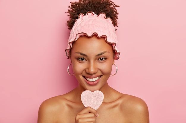Linda jovem afro-americana com pele escura, segura uma esponja cosmética para remover a maquiagem, vai tomar banho e relaxar após um árduo dia de trabalho, usa uma bandana rosa suave para proteger da umidade