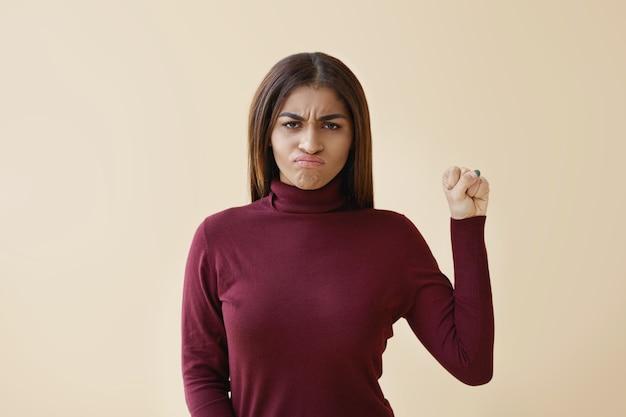 Linda jovem afro-americana com pescoço de tartaruga e determinada expressão de raiva, mantendo o punho erguido em busca de força feminina e independente, lutando contra a injustiça e a violência