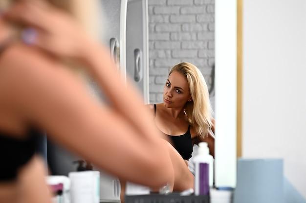 Linda jovem ajeitando o cabelo se olhando no espelho