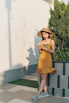 Linda jovem alegre asiática passando um bom tempo no parque, lendo um livro de papel em pé