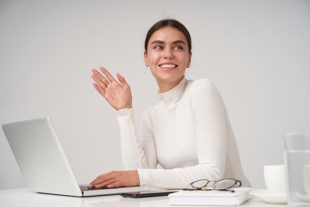 Linda jovem alegre de cabelos escuros com maquiagem natural, levantando a mão em um gesto de olá e olhando positivamente para o lado com um sorriso amigável, isolada sobre a parede branca