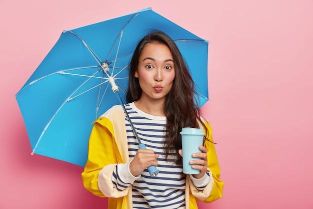 Linda jovem aluna asiática, a caminho da universidade durante um dia chuvoso, protege-se da umidade com guarda-chuva e capa de chuva