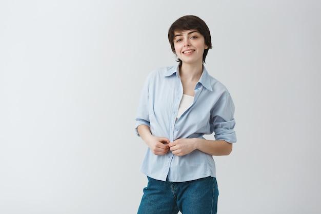 Linda jovem aluna com cabelo escuro curto, sorrindo brilhantemente, abotoando a camisa e olhando com uma expressão feliz e confiante.