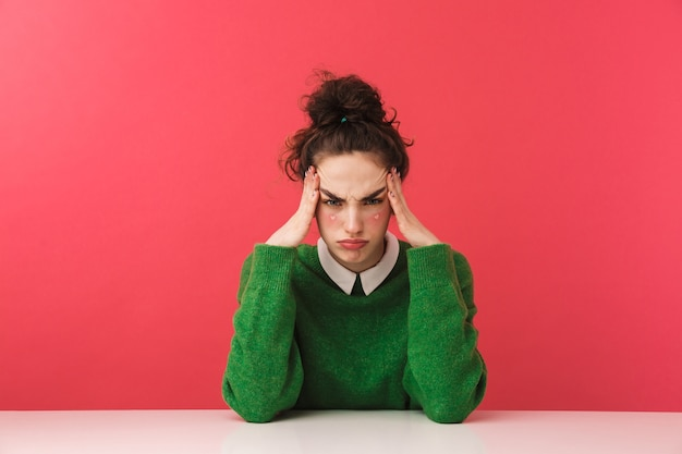 Linda jovem aluna entediada sentada à mesa isolada