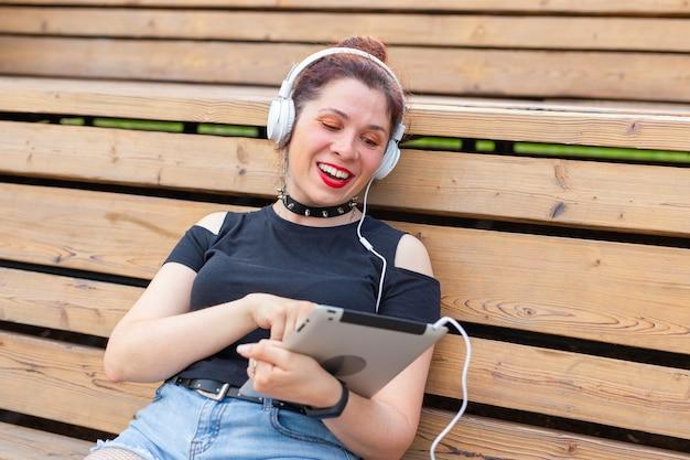 Linda jovem aluna está estudando usando um tablet e fones de ouvido enquanto está sentada em um parque na