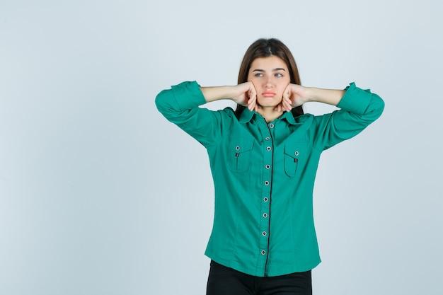 Linda jovem amuada com as bochechas apoiadas nas mãos na camisa verde e olhando para baixo, vista frontal.