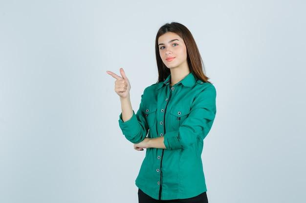 Linda jovem apontando para a esquerda com uma camisa verde e olhando confiante, vista frontal.