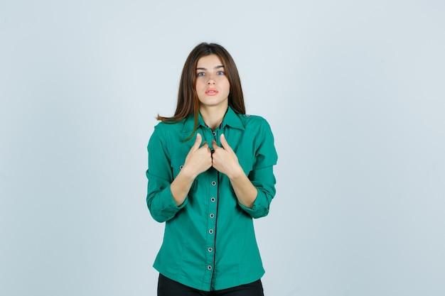 Linda jovem apontando para si mesma em uma camisa verde e olhando confusa, vista frontal.