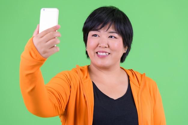 Linda jovem asiática com excesso de peso pronta para a academia contra chroma key com parede verde