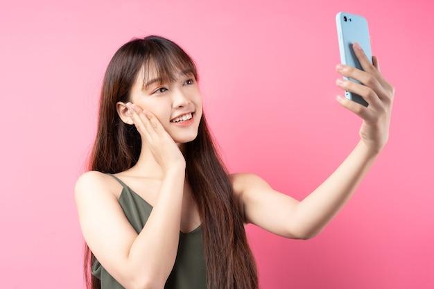 Linda jovem asiática usando o telefone na parede rosa