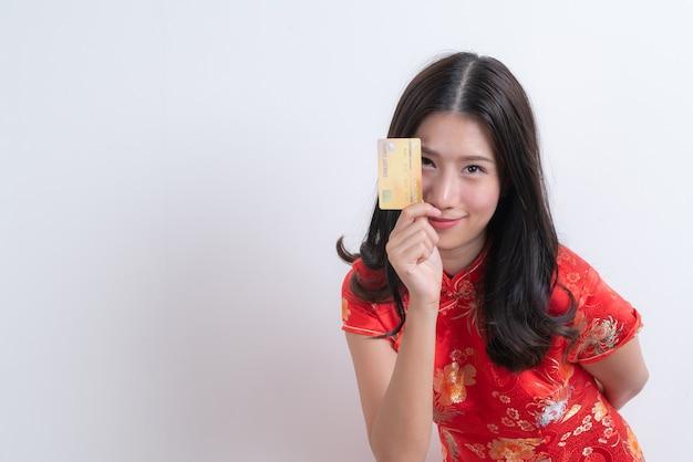 Linda jovem asiática usando um vestido tradicional chinês vermelho segurando um cartão de crédito