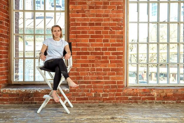 Linda jovem atrevida está sentado em uma cadeira perto da parede de tijolo.