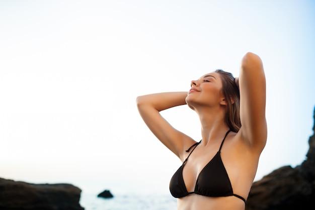 Linda jovem baseia-se na praia de manhã