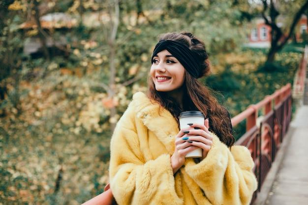 Linda jovem bebe café em um copo na rua, ri e sorri