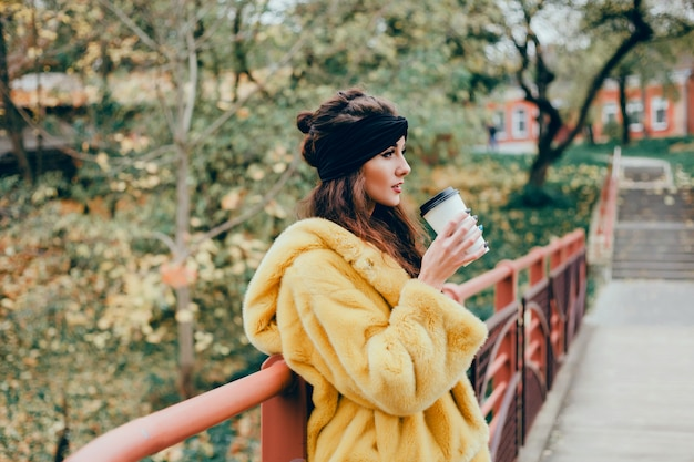 Linda jovem bebe café em um copo na rua