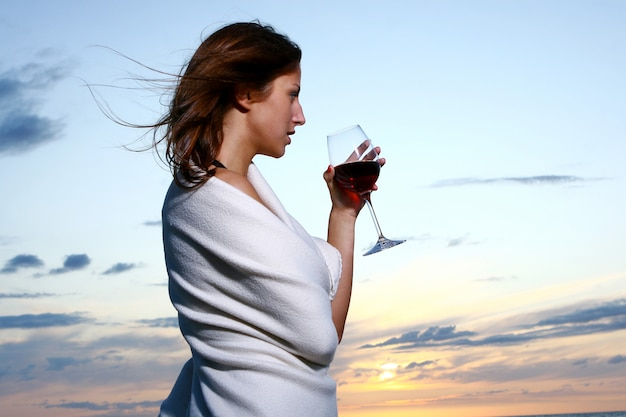 Linda jovem bebendo vinho na praia