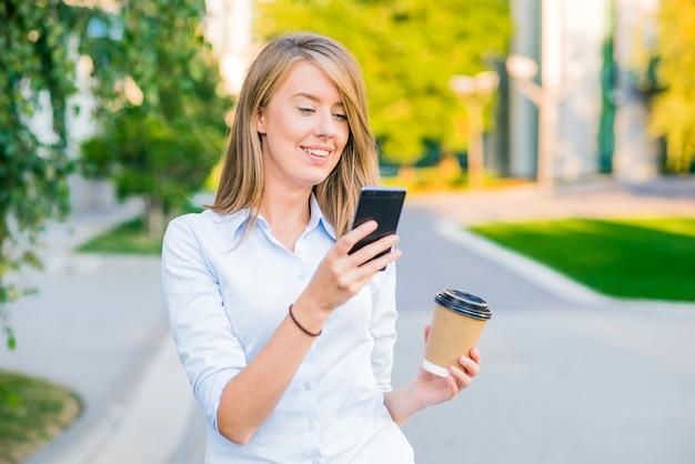 Linda jovem bonita com mensagens de cabelo loiro no telefone inteligente no fundo da rua da cidade. menina bonita que conversa com telefone inteligente no toque do sol.