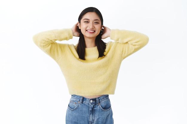 Linda jovem carismática garota asiática em um suéter amarelo escovando o cabelo atrás das orelhas fofa, sorrindo kawaii, expressando emoções despreocupadas e felizes, sendo positiva, aproveitando os dias ensolarados de primavera