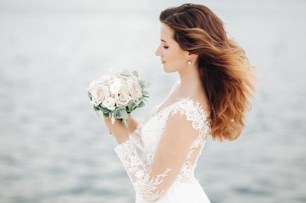 Linda jovem caucasiana com um buquê de noiva nas mãos e olha para ele