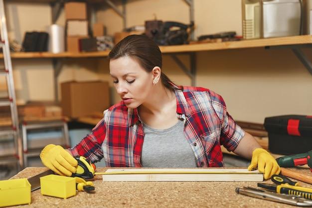 Linda jovem caucasiana de cabelos castanhos com camisa xadrez, camiseta cinza, luvas amarelas trabalhando em uma oficina de carpintaria em uma mesa de madeira com diferentes ferramentas, medindo o comprimento da barra por fita métrica